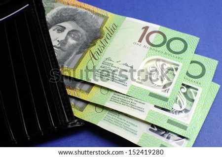 Three hundred Australian dollar green and yellow notes folding out from black wallet. - stock photo