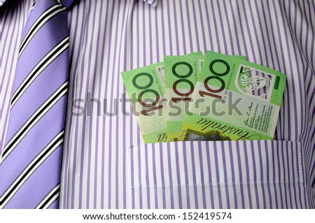 Three hundred dollar notes in font pocket of business man's shirt, with purple stripe tie. - stock photo