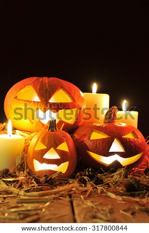 three illuminated halloween pumpkins and straw on old weathered wooden board in front of black background in red light - stock photo