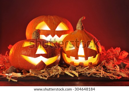 three illuminated halloween pumpkins and straw on old weathered wooden board in front of red background - stock photo
