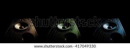 three images sound speaker of tinted in different colors on a black background isolated - stock photo