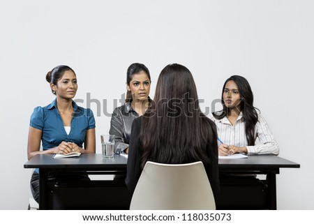 Three Indian colleagues from HR department interview a young female applicant.