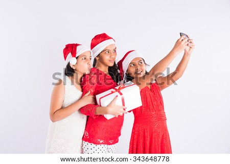 three indian girls with santa hat and gift box, posing for selfie with mobile, cheerful pose, close friends, indian family and christmas, indian kids and christmas, isolated on white background - stock photo