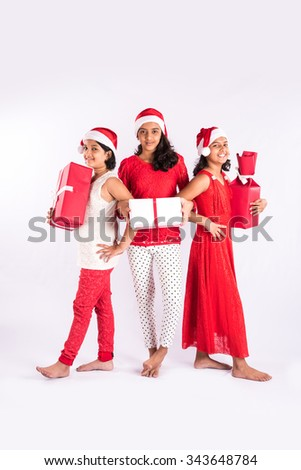 three indian girls with santa hat and gifts in hand, standing close, cheerful pose, close friends, indian family and christmas, indian kids and christmas, isolated on white background - stock photo