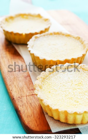 Three indulgent lemon tarts served on a wooden platter with a turquoise background