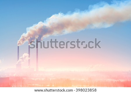 Three industrial chimney with smoke against the sky with sunlight - stock photo