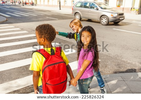 Three international kids ready to cross road - stock photo