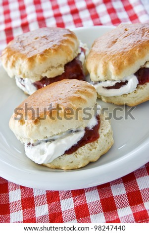 Three jam and cream scones on a white plate - stock photo