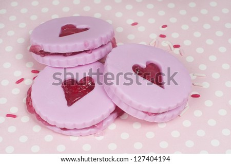 Three jam cookies with hearts and sprinkles. valentine background