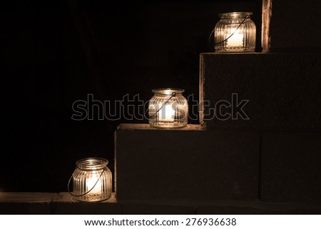 three jar lights on a tiered cement wall steps on black background of darkness