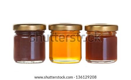 Three jar of jam and honey on white background - stock photo