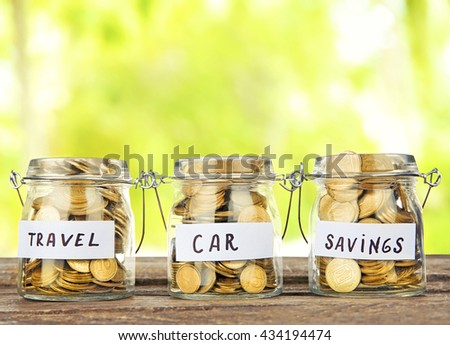 Three jars for different needs full of coins on nature background - stock photo