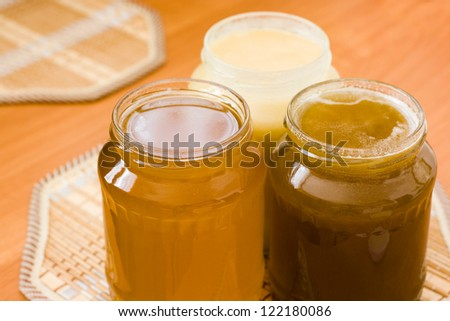 Three jars of sweet honey on the table with decorative elements