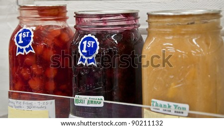 Three jars of various homemade fruit pie filling with first place ribbons are in this home canned competition at a county fair. - stock photo