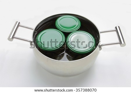 Three jars with green lids in steel pot. Isolated on white background - stock photo