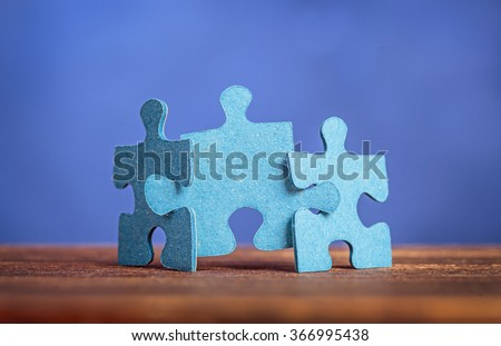 Three jigsaw puzzle pieces on a table joint together against blue background. Shallow depth of field