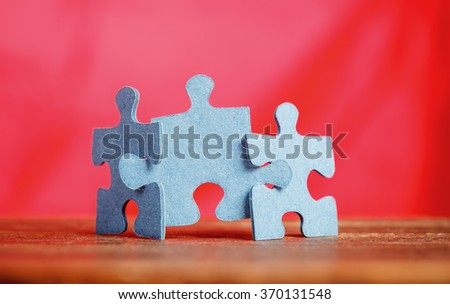 Three jigsaw puzzle pieces on a table joint together over red background. Shallow depth of field - stock photo