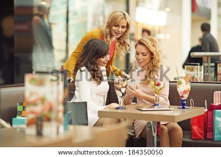 Three joyful women during short coffee break - stock photo