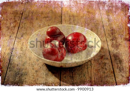 three juicy fruits in a white glass bowl on a wooden floor