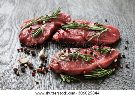 Three juicy raw beef steaks garnished with rosemary twigs, garlic and peppercorns - stock photo