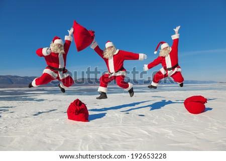 Three Jumping Santa Claus outdoors  - stock photo