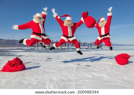 Three Jumping Santa Claus outdoors ,multiexposition, shooting was conducted in a sunny day on lake Baikal - stock photo