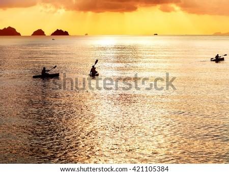 three kayak float at sunset - stock photo