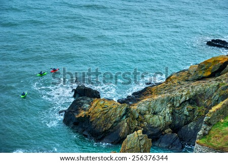 Three kayaks seen from the top of a high rocky cliff - stock photo
