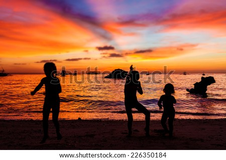 three kid silhouettes on sunset sea background - stock photo