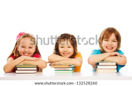 Three kids boy and girls laying on pile of books on the table, smiling, laughing, isolated on white
