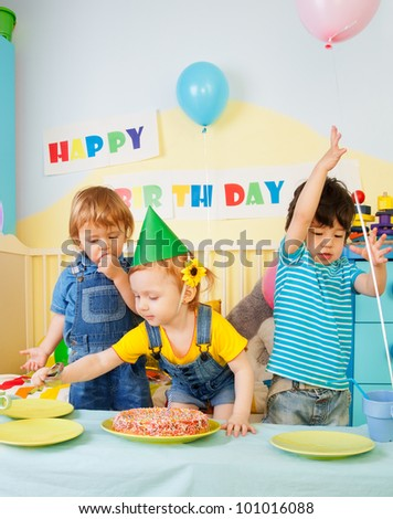 Three kids having fun on the birthday party - two boys and one girl - stock photo