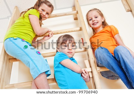 Three kids in bright clothing up high on the wall bars - stock photo