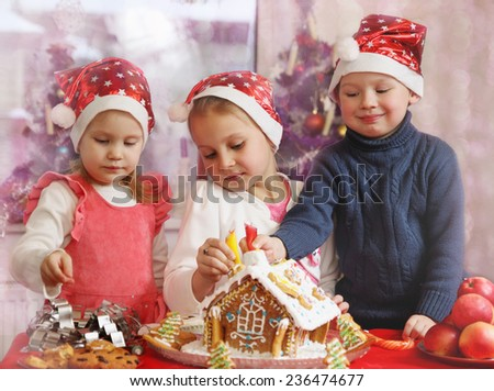 Three kids in caps decorated gingerbread house