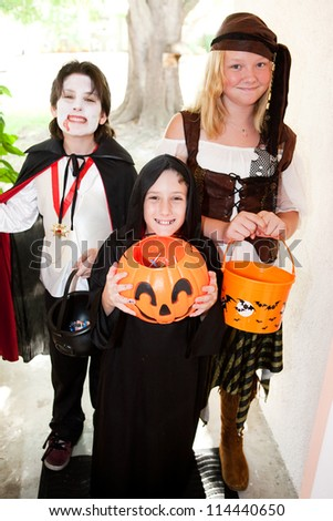 Three kids in Halloween costumes going trick or treating door-to-door.  Focus on little boy in front.