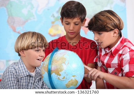 Three kids learning geography. - stock photo