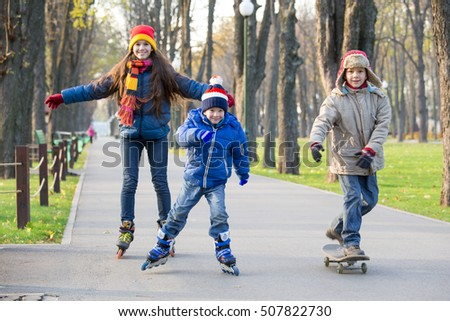 Three kids learning to ride in autumn park on roller skates and skateboard