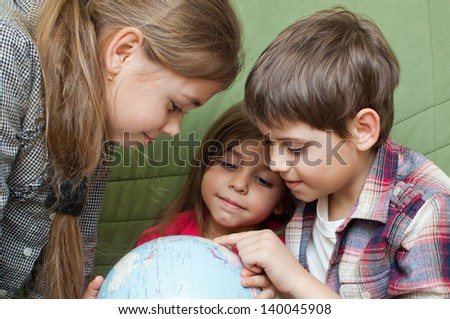 Three kids looking closely at a world globe - stock photo