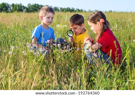 Three kids looking to flower through a magnifying glass, outdoor - stock photo