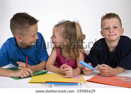 Three kids lying on the floor coloring on bright colored paper.