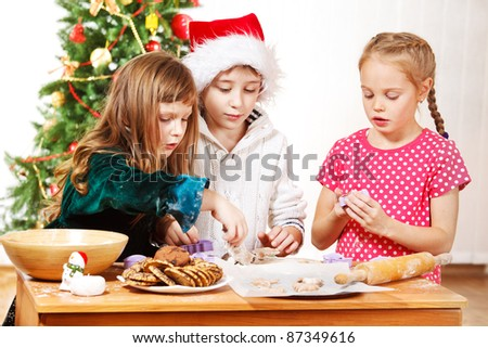 Three kids making Christmas cookies