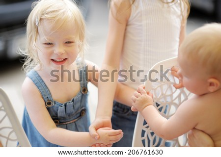 Three kids playing together outdoors - stock photo
