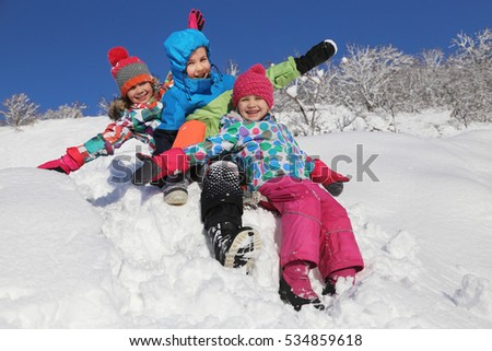 three kids  ride in the snow on  sled