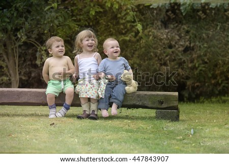 three kids seated on a beam