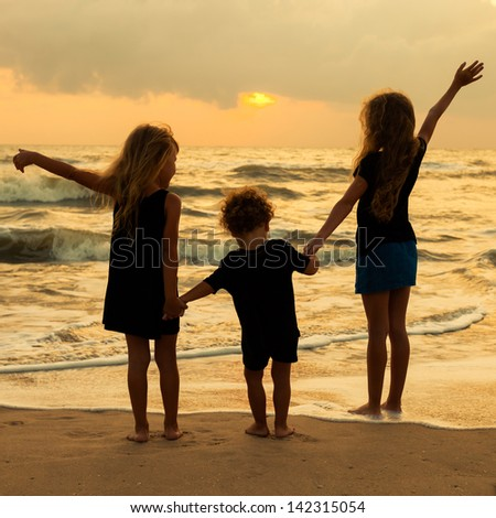 three kids silhouettes standing on beach at sunset - stock photo