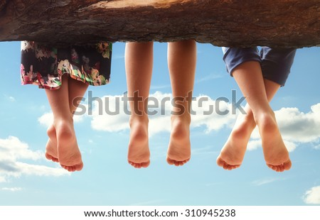 Three kids sitting in a tree dangling their feet against a blue sky in summer concept for family, friends, carefree and vacations - stock photo