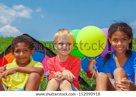 Three kids sitting on grass