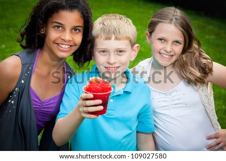 Three kids smile in the sunshine, the boy holding a snow cone. - stock photo