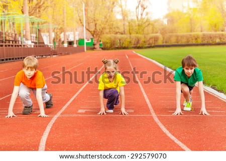 Three kids stand with bended knee ready to run - stock photo