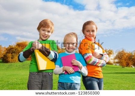 three kids standing with books in autumn park