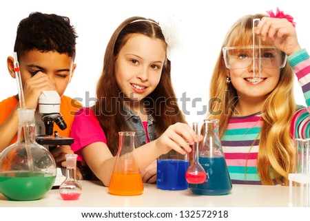 Three kids, two girls blond and brunet with test tubes and flasks conducting experiments and black boy with microscope, isolated on white - stock photo